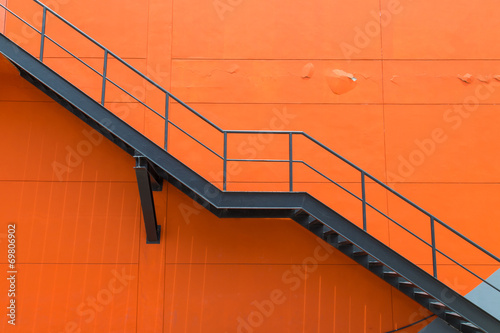 Metal fire escape or emergency exit on Orange Wall of Buliding - 69806902