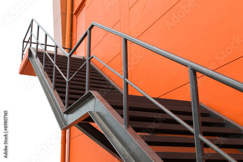 Leinwanddruck Bild Metal fire escape or emergency exit on Orange Wall of Buliding W