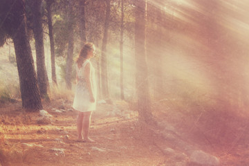 surreal photo of young woman standing in forest. image is textur