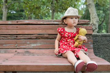 Cute Smiling Young Girl Hugging Her Teddy Bear on Bench Outside