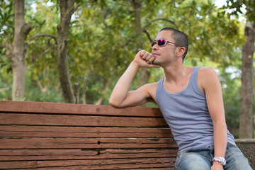 ベンチで頬杖をつく男性