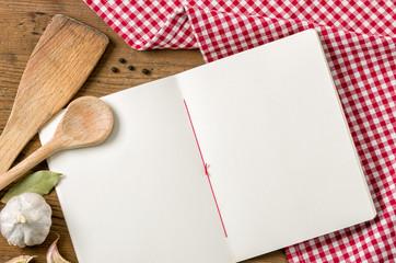 Heft mit Kochlöffeln auf einem rot karierten Tischtuch