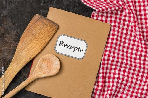 Leinwanddruck Bild Rezeptbuch mit Kochlöffeln auf einem rot karierten Tischtuch
