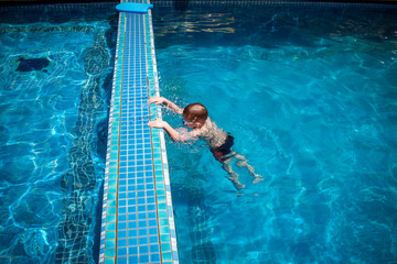 boy swims into blue swimming pool in resort. Koh Samui