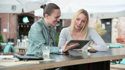 Two female friends with tablet computer sitting in cafe