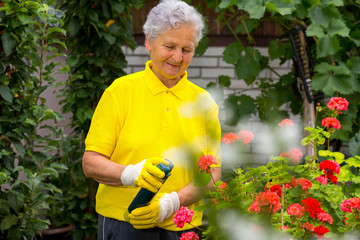 Portrait of pretty senior woman with flowers-sprayed flowers