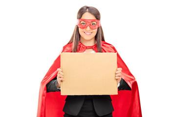 Female superhero holding a blank cardboard sign