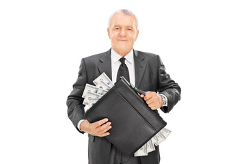 Successful businessman holding briefcase full of money