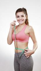 brunette woman measuring abdomen with tape