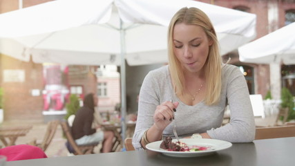 Woman eating dessert at an outdoor restaurant