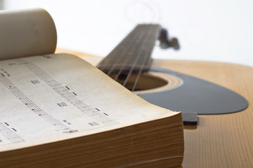 Color photo of an strings acoustic guitar and music note