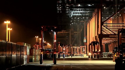 Container ship loading and unloading at night