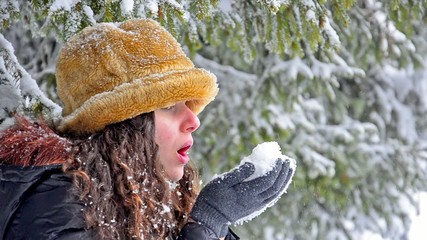 Teen girl with fur hat blowing snowflakes