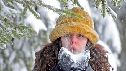 Girl Blows snow under pine into the camera