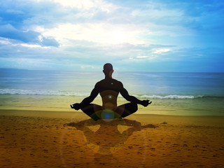Silhouette of a male figure meditating on the beach
