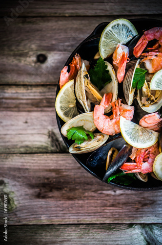 Poster Mix of mussels,clams and shrimps on wooden background