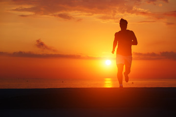 Silhouette of attractive jogger in action running on the beach