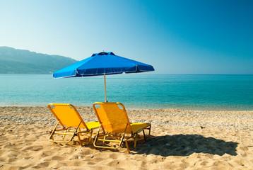 Yellow sunbeds and blue umbrella in Corfu Island, Greece