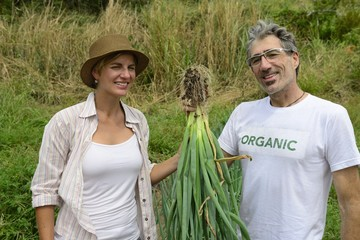 Couple of organic farmers showing green onion