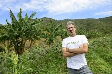 Organic farmer in front of farmland