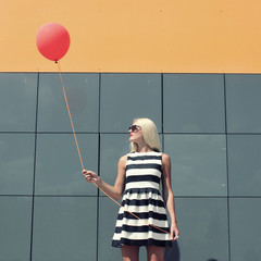 young happy trendy girl  with a red balloon.