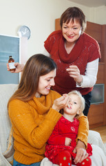 Young woman with mature mother giving  syrup to unwell toddler