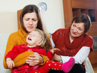 Mature woman comforting adult daughter with crying baby