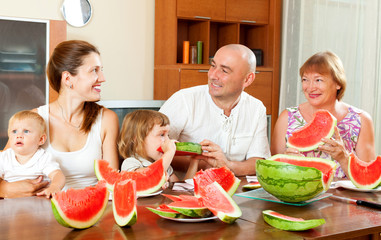 Smiling happy three generations family eating watermelon  over