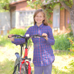 Teenager girl with bicycle in countryside outdoors