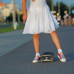 teenager legs in sneakers with skateboard at sunset.