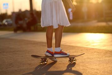teenage girl riding a skateboard on the evening street