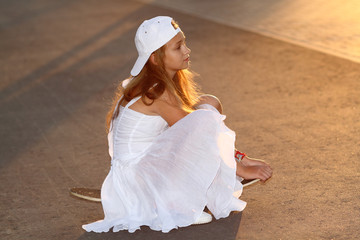 Teenager girl in a white dress on a skateboard at sunset.
