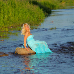 mature beautiful blonde in vintage dress having fun in the sea.