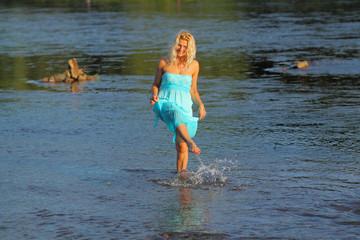 mature beautiful blonde in vintage dress having fun in the sea.