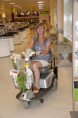 Woman using a mobility scooter to shop at a supermarket