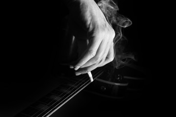 Composition of guitar and man's hand with cigarette smoking