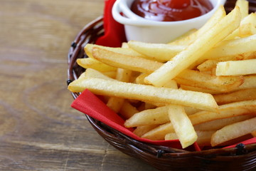 Traditional French fries with ketchup in a wicker basket