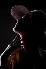 unknown woman with a hat and face in shadow touching her neck