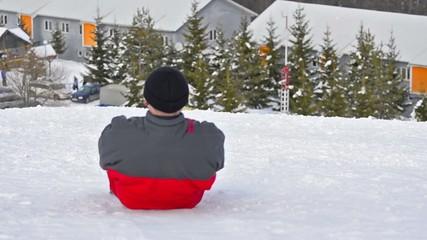 Man having fun sledging down the mountain ski slope