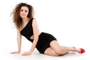 A girl in a black dress in the studio on a white background.