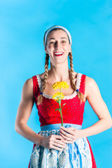 Frau in Dirndl Tracht hält Blume