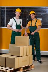 Men with fork pallet truck full of boxes