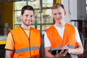 Men in orange protective vest working at factory