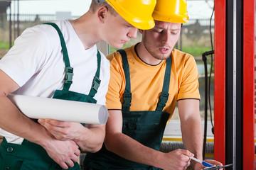 Teamwork of two factory engineers