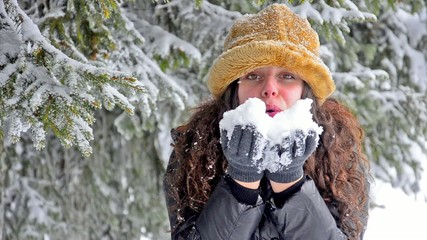 Attractive Girl Blowing Snow Flakes At Camera