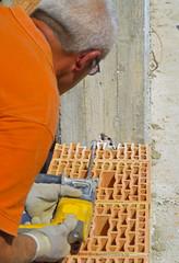 Mason drills a hole with a power drill on a column