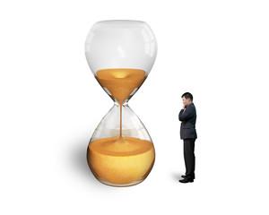 standing man watching the hourglass