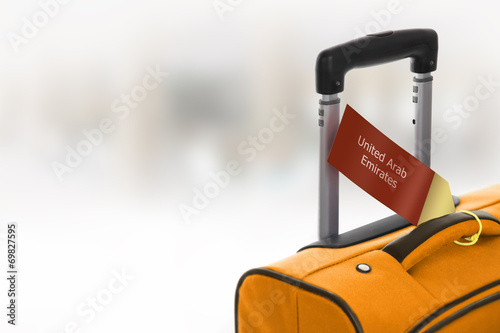 canvas print picture United Arab Emirates. Orange suitcase with label at airport.