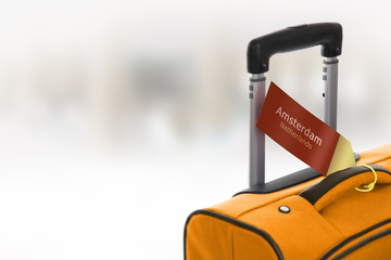 Amsterdam, Netherlands. Orange suitcase with label at airport.