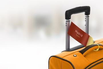 Madrid, Spain. Orange suitcase with label at airport.
